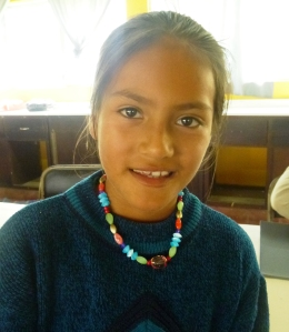 Erika models the necklace she made after the first day of the workshop.