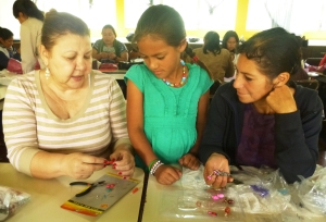 Maria (left) helps Erika become comfortable with the jewelry tools, while her mother looks on.