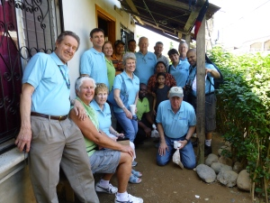 Our Board members and a few staff with Carmen outside her home which she has been able to invest in with a Home Improvement Loan
